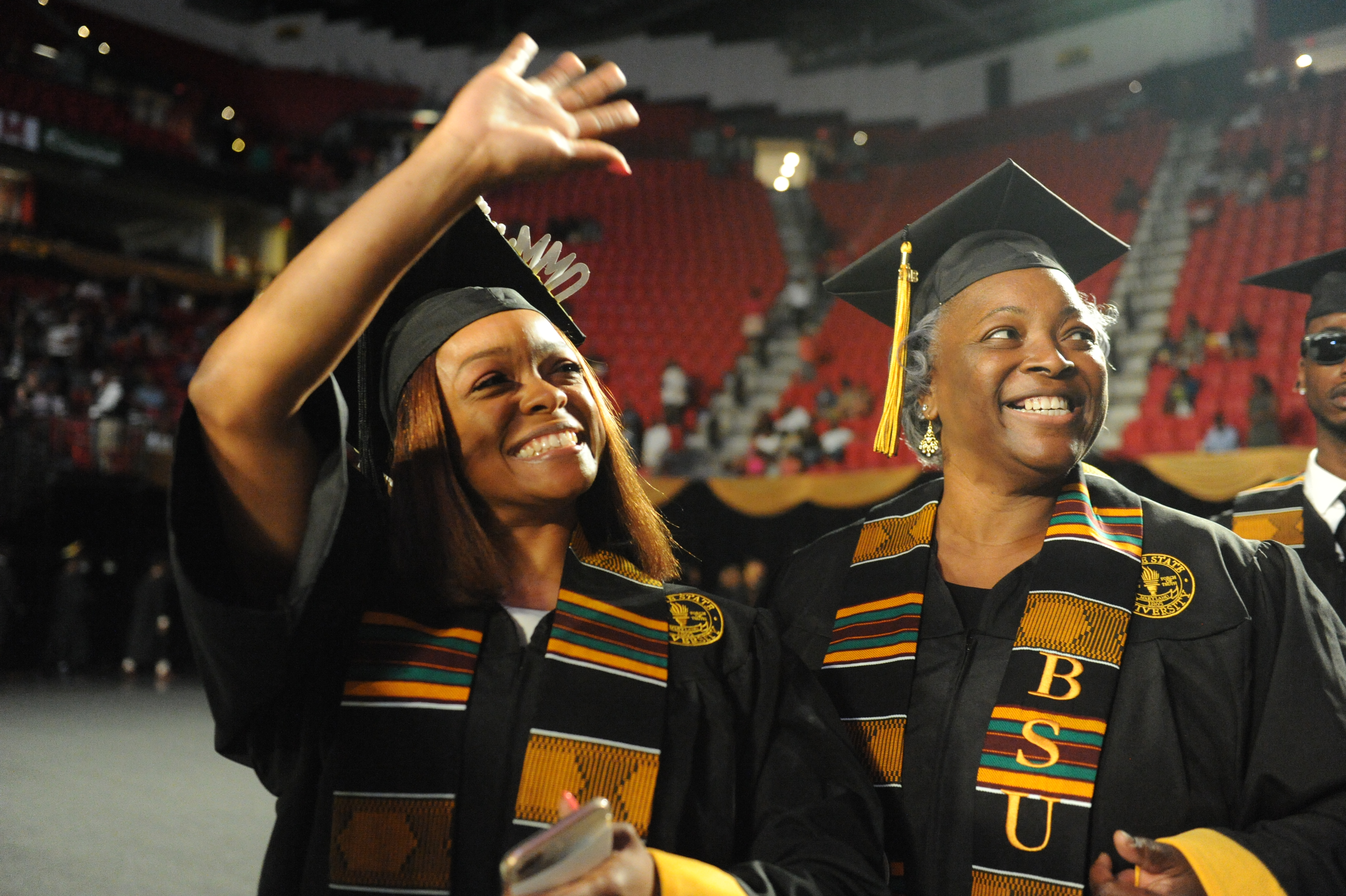 Two female graduates smile and look up at their families