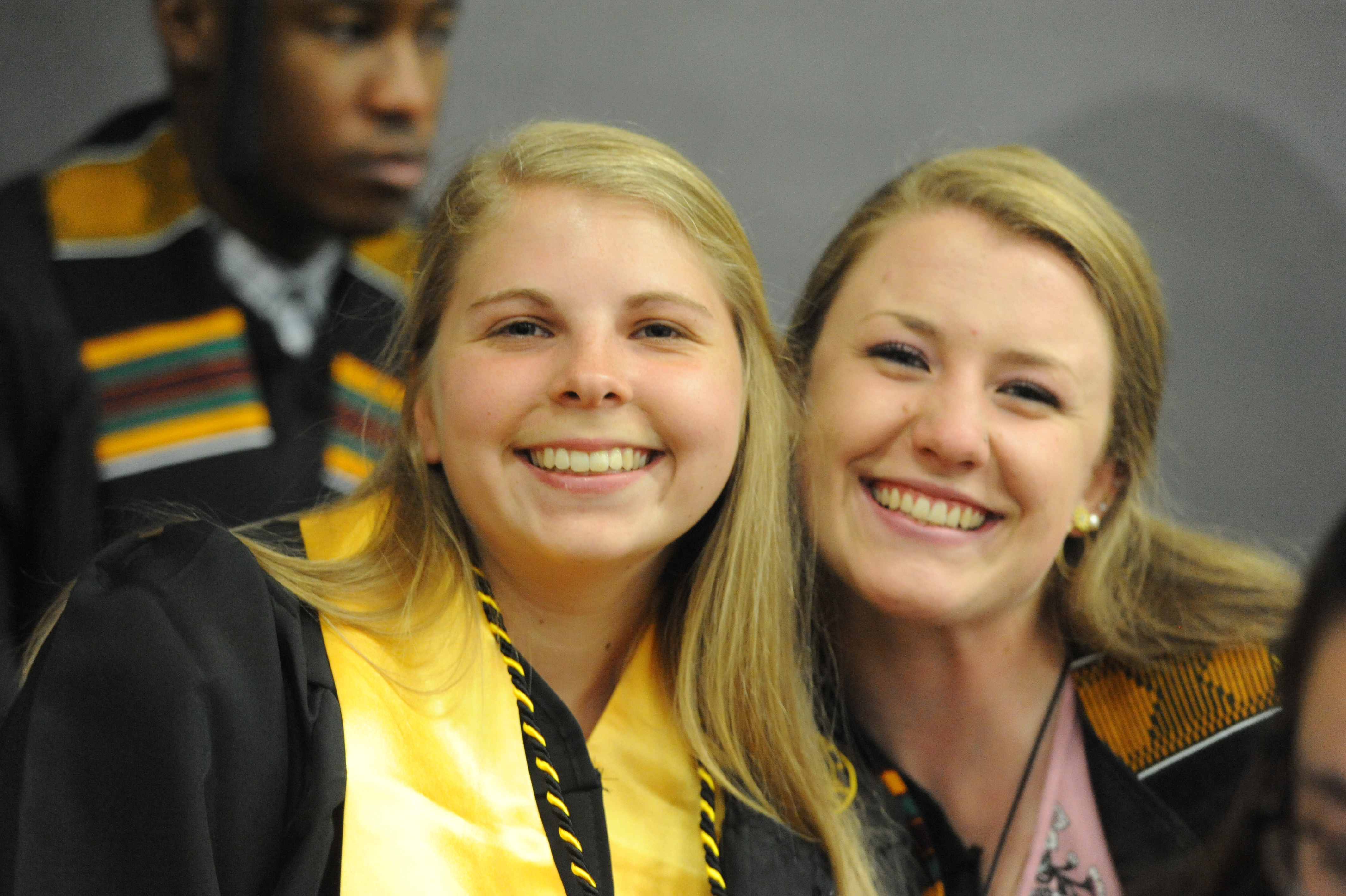 Two female graduates smile and pose for the camera