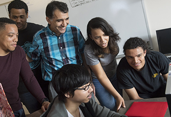 Diverse Students and Professor Huddle Around Computer Screen