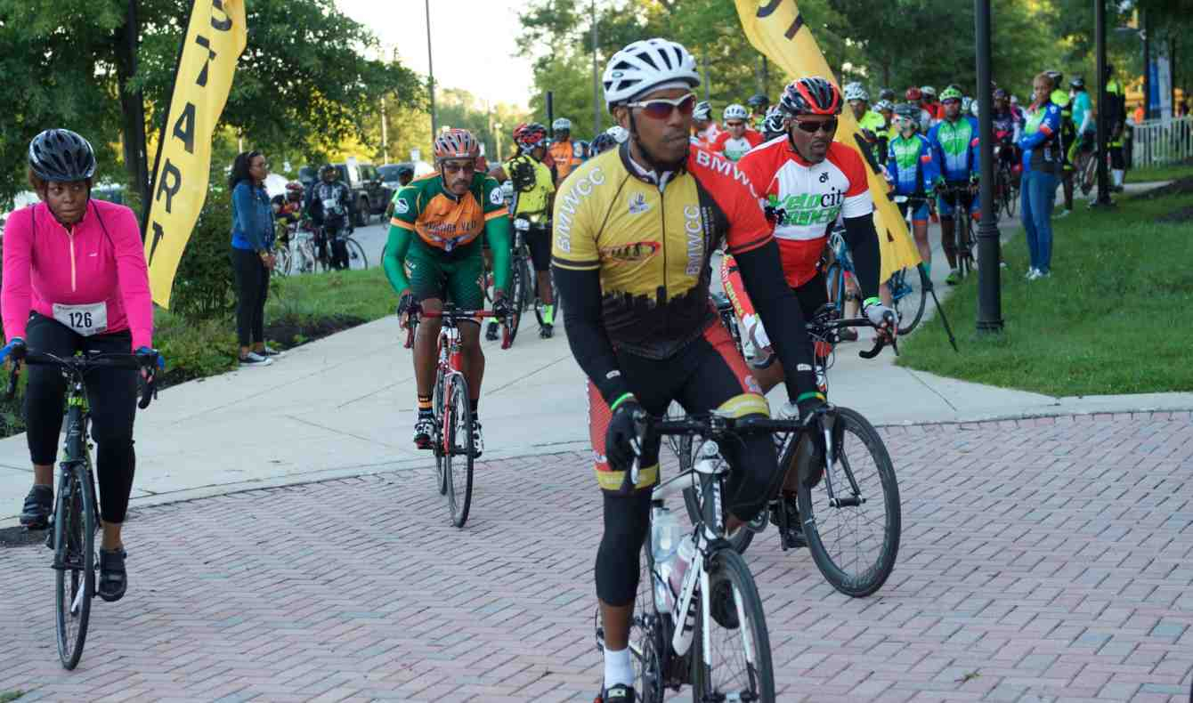 President Breaux Leads a Group of Cyclists in Bike Tour
