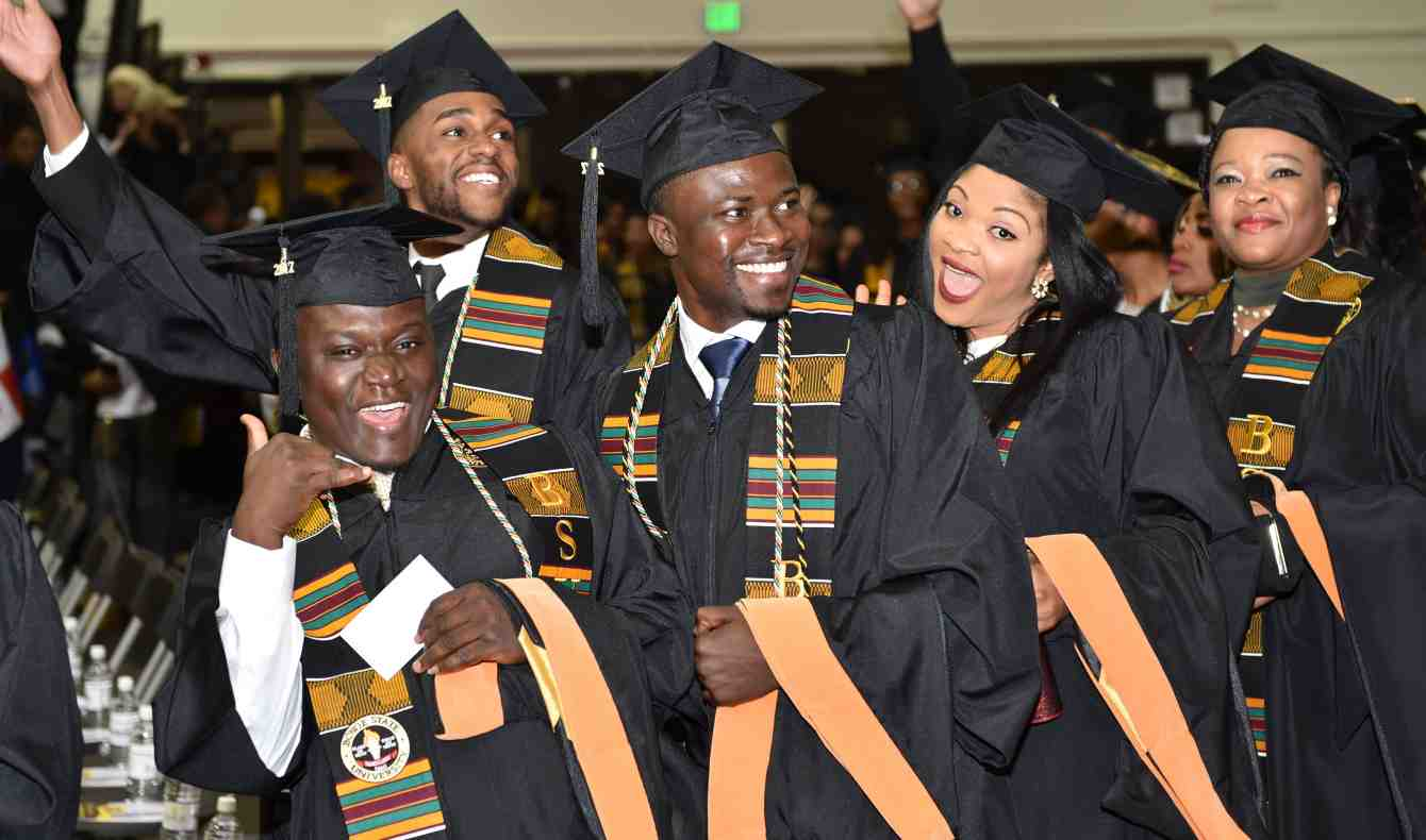 Picture of Three Men and Two Women Graduates Smiling at Commencement