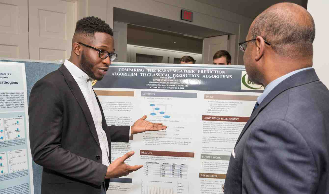 Jesuye David presents his poster to a professional at the Posters on the Hill