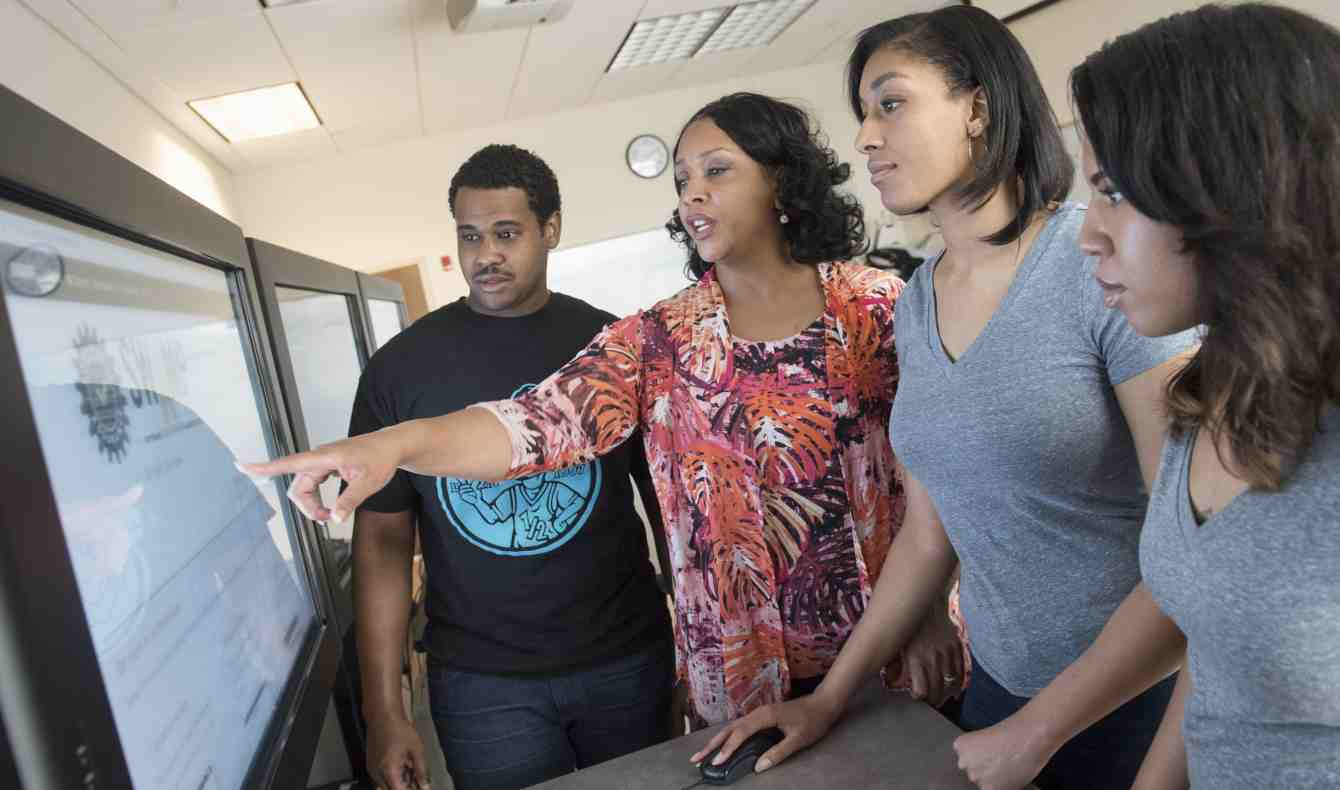 Diverse Students Stand with Professor Around a Computer Screen